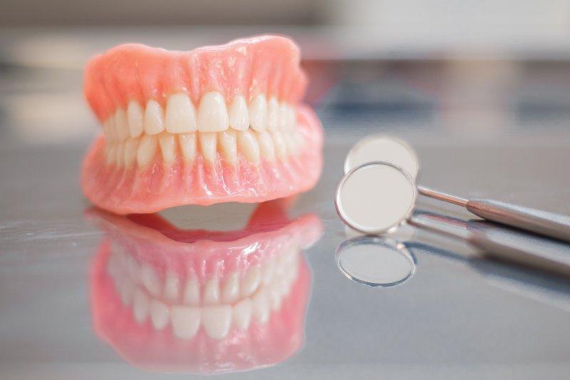 Full dentures lying on table next to dental mirror